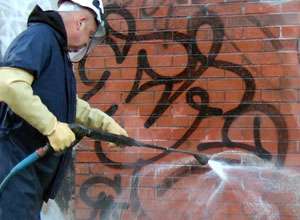 Man removing graffiti from brick wall with hose